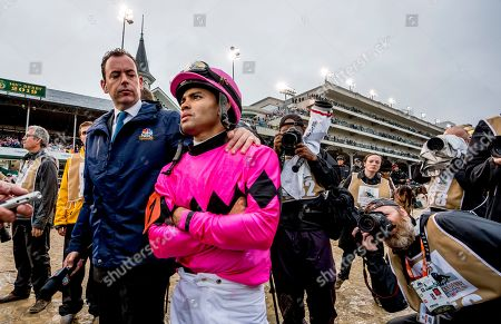 Louisville, Kentucky, U.S. - NBC interviewer Nick Luck tries to offer jockey Luis Saez (pink cap) some consolation as he waited out a 23-minute objection. His mount Maximum Security would be disqualified and Flavien Prat and his mount, Country House, were awarded the win in the Kentucky Derby on Kentucky Derby Day at Churchill Downs