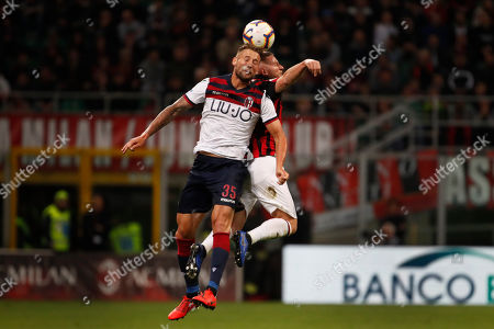 AC Milan's Ignazio Abate, right, goes for a header with Bologna's Mitchell Dijks during the Italian Serie A soccer match between AC Milan and Bologna at the San Siro stadium, in Milan, Italy
