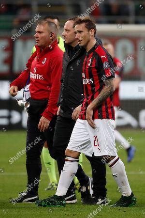 AC Milan's Lucas Biglia, right, leaves the pitch after being injured during the Italian Serie A soccer match between AC Milan and Bologna at the San Siro stadium, in Milan, Italy