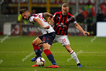 Bologna's Mitchell Dijks, left, fights for the ball with AC Milan's Ignazio Abate during the Italian Serie A soccer match between AC Milan and Bologna at the San Siro stadium, in Milan, Italy