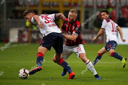 Stock Photo of Bologna's Mitchell Dijks, left, fights for the ball with AC Milan's Ignazio Abate during the Italian Serie A soccer match between AC Milan and Bologna at the San Siro stadium, in Milan, Italy