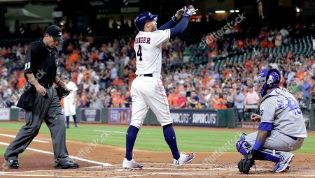 Houston Astros designated hitter George Springer (4) crosses the plate between umpire Pat Hoberb, left, and Kansas City Royals catcher Martin Maldonado, right, after hitting a home run during the first inning of a baseball game, in Houston