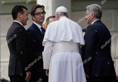 Pope Francis is welcomed by North Macedonia Prime Minister Zoran Zaev, left, President elect Stevo Pendarovski and outgoing President Gjorge Ivanov, after landing at the airport of Skopje, North Macedonia,. Francis, who is on a three-day trip to the Balkans, is visiting North Macedonia for the first-ever papal visit to the country