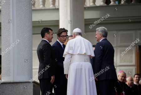 Pope Francis is welcomed by North Macedonia Prime Minister Zoran Zaev, left, President elect Stevo Pendarovski and outgoing President Gjorge Ivanov, right, after landing at the airport of Skopje, North Macedonia,. Francis, who is on a three-day trip to the Balkans, is visiting North Macedonia for the first-ever papal visit to the country
