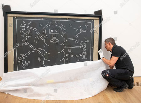 A museum employee works at the artwork 'Subway Drawings' by the American Artist Keith Haring during the installation of the exhibition 'Forever Young - 10 Years of Museum Brandhorst' at the Museum Brandhorst in Munich, Germany, 07 May 2019. The exhibition comprises around 250 works by 45 artists, including Andy Warhol, Cy Twombly, Bruce Nauman, Cady Noland, and Wolfgang Tillmans, and will open on 23 May.