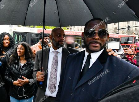 Musician R. Kelly, right, leaves the Leighton Criminal Court building after a hearing in his sex-abuse case, in Chicago