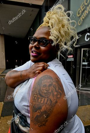 Reshynda Baker, from Louisville, Ky., shows off her R. Kelly tattoo as she waits to see him outside Leighton Criminal Court building where he appeared for a hearing in his sex-abuse case, in Chicago
