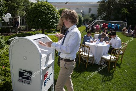 Stock Photo of Invited guests write cards and drop them in a mailbox in the Jacqueline Kennedy Garden as part of a one year anniversary event for the first lady's Be Best initiative in the Rose Garden of the White House, in Washington