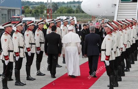 Pope Francis is flanked by North Macedonia's outgoing president Gjorge Ivanov, right, and Premier Zoran Zaev, as they review the honor guard during a farewell ceremony at the Skopje airport,. Francis made the first-ever papal visit to North Macedonia on Tuesday and sought to encourage its efforts to integrate into European institutions after its name change resolved a decades-long dispute with Greece
