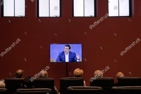 Stock Picture of Alexis Tsipras, Euklid Tsakalotos. People watch a TV screen as Greek Prime Minister Alexis Tsipras announces bailout relief measures during a press conference, in Athens, on . Greece's left-wing prime minister has promised crisis-weary voters a series of tax-relief measures ahead of elections, after outperforming budget targets set by bailout creditors