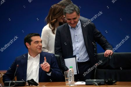Alexis Tsipras, Euklid Tsakalotos. Greek Prime Minister Alexis Tsipras, left, speaks with Greek Financial Minister Euklid Tsakalotos as they arrive to take part on a new conference, in Athens, on . Greece's left-wing prime minister has promised crisis-weary voters a series of tax-relief measures ahead of elections, after outperforming budget targets set by bailout creditors