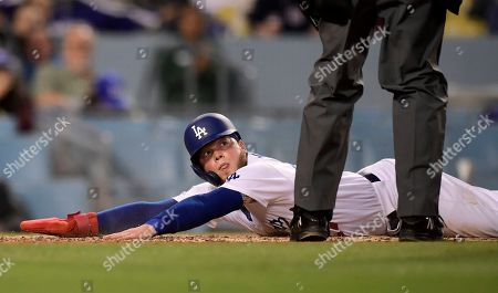 Alex Verdugo, Andy Fletcher. Los Angeles Dodgers' Alex Verdugo, left, waits for the call from home plate umpire Andy Fletcher after scoring on a single by Justin Turner during the second inning of a baseball game, in Los Angeles