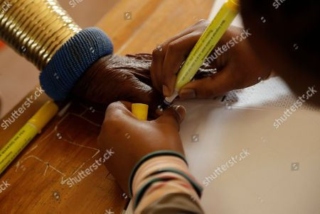 Esther Mahlangu, a contemporary South African artist, has her thumb ink-marked before casting her vote in presidential and parliamentary elections at a polling station at KwaMhlanga in Mpumalanga, South Africa, . South Africans have started voting in presidential and parliamentary elections amid issues of corruption and unemployment. It is 25 years after the end of apartheid, but despite the demise of the system of racial discrimination the country remains divided by economic inequality