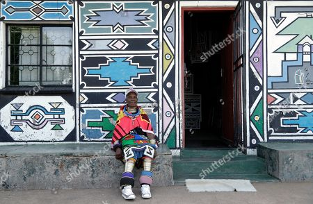 Esther Mahlangu, a contemporary South African artist, sits outside her house after voting at a polling station during elections at KwaMhlanga in Mpumalanga, South Africa, . South Africans are voting Wednesday in a national election that pits President Cyril Ramaphosa's ruling African National Congress against top opposition parties Democratic Alliance and Economic Freedom Fighters, 25 years after the end of apartheid