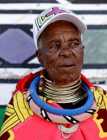Esther Mahlangu, a contemporary South African artist, stands outside her house after voting at a polling station during elections at KwaMhlanga in Mpumalanga, South Africa, . South Africans are voting Wednesday in a national election that pits President Cyril Ramaphosa's ruling African National Congress against top opposition parties Democratic Alliance and Economic Freedom Fighters, 25 years after the end of apartheid