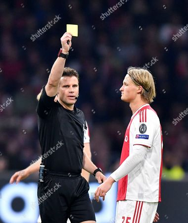 Referee Felix Brych, left, shows a yellow card to Ajax's Kasper Dolberg during the Champions League semifinal second leg soccer match between Ajax and Tottenham Hotspur at the Johan Cruyff ArenA in Amsterdam, Netherlands