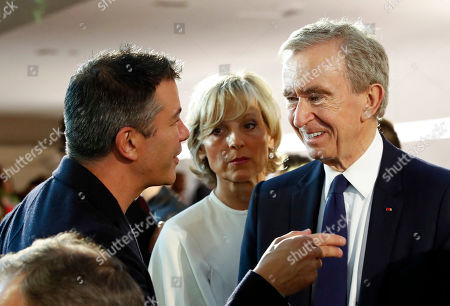 Stock Photo of US billionaire and Co-founder of Scour, Red Swoosh and Uber Travis Kalanick (L) chats with Chief Executive of LVMH Bernard Arnault (R) and Helene Mercier-Arnault (C) in the audience before the start of French designer Nicolas Ghesquiere fashion show for the Louis Vuitton label during the Louis Vuitton Cruise 2020 Show at the TWA Flight Center of John F. Kennedy International Airport in New York, New York, USA, 08 May 2019.