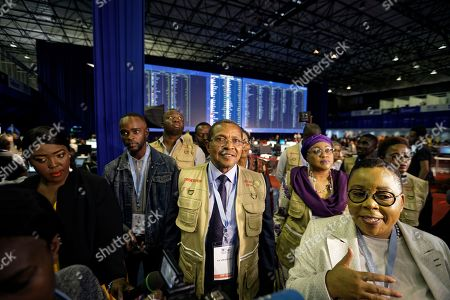 Former President of Tanzania Jakaya Kikwete, center, who is leading the African Union Election Observation Mission, is shown the Independent Electoral Commission (IEC) Results Center in Pretoria, South Africa . South Africans voted Wednesday in a national election that pits President Cyril Ramaphosa's ruling African National Congress against top opposition parties Democratic Alliance and Economic Freedom Fighters, 25 years after the end of apartheid