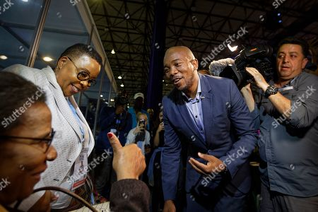 Mmusi Maimane, leader of the largest opposition party, the Democratic Alliance, is greeted by a supporter as he visits the Independent Electoral Commission Results Center in Pretoria, South Africa . South Africans voted Wednesday in a national election and preliminary results show that the ruling African National Congress party (ANC) has an early lead in the national elections but has seen its share of the vote drop significantly