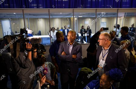 Mmusi Maimane, centre, leader of the largest opposition party, the Democratic Alliance, speaks with party workers as he visits the Independent Electoral Commission Results Center in Pretoria, South Africa . South Africans voted Wednesday in a national election and preliminary results show that the ruling African National Congress party (ANC) has an early lead in the national elections but has seen its share of the vote drop significantly