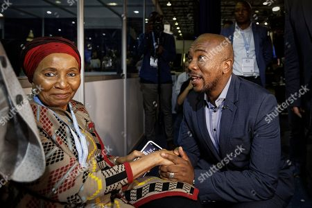 Mmusi Maimane, leader of the largest opposition party, the Democratic Alliance, greets a supporter, left, as he visits the Independent Electoral Commission Results Center in Pretoria, South Africa . South Africans voted Wednesday in a national election and preliminary results show that the ruling African National Congress party (ANC) has an early lead in the national elections but has seen its share of the vote drop significantly