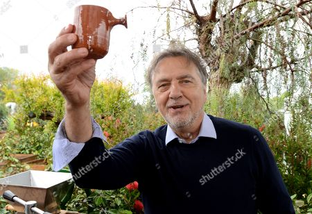 Raymond Blanc enjoys the fruits of his labour, after squeezing Oranges in the 'Villaggio Verde' 'Orange Express' garden