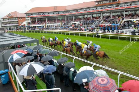Stock Photo of Runners in the TMT Group Handicap at Chester won by Sam Cooke and Harry Bentley pass the rain soaked crowds and stands at Chester.