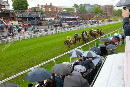 Runners in the TMT Group Handicap at Chester won by Sam Cooke and Harry Bentley pass the rain soaked crowds and stands at Chester.