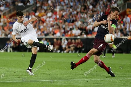Carlos Soler of Valencia shoots at goal past Laurent Koscielny of Arsenal