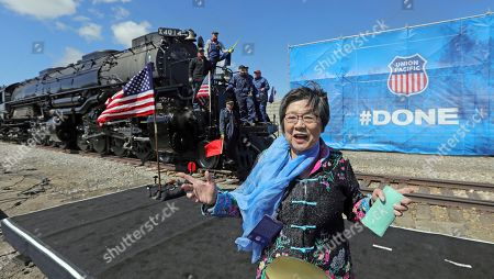 Margaret Yee, whose ancestors helped build the railroad, pose in front of the the Big Boy, No. 4014 during the commemoration of the 150th anniversary of the Transcontinental Railroad completion at Union Station, in Ogden, Utah. Yee, helped tap a ceremonial spike alongside Utah Gov. Gary Herbert and a descendant of Union Pacific's chief engineer on the project at the event Thursday in Ogden, Utah