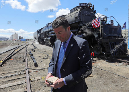 Vince Hoffarth, Special Agent In Charge Union Pacific Railroad Police, holds a box of ashes in front of the Big Boy, No. 4014 following the celebration of the 150th anniversary of the completion of the Transcontinental Railroad at Union Station, in Ogden, Utah. Attendees included a British family that traveled to Utah to fulfill a train engineer's dying wish last year to have his ashes put in the boiler of the Big Boy train. Utah Gov. Gary Herbert held a box with the man's ashes at the ceremony and promised to fulfill the wish. Several thousand train lovers have gathered in Utah to catch a glimpse of a pair of restored 1940s-era steam engines