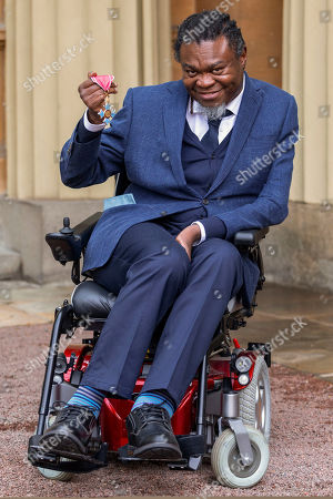 Artist Yinka Shonibare proudly displays his OBE for services to art awarded at an investiture ceremony conducted by Prince William at Buckingham Palace