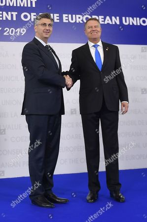 Croatian Prime Minister Andrej Plenkovic, left, is welcomed by Romanian President Klaus Ioannis