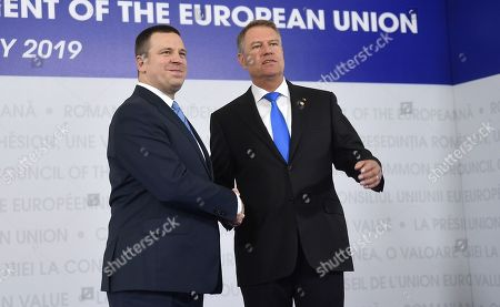 Estonian Prime Minister Juri Ratas, left, is welcomed by Romanian President Klaus Ioannis