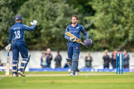 Stock Photo of Scotland's Donald MacLeod celebrates with Craig Wallace (#18) after scoring 100 runs during the One Day International match between Scotland and Afghanistan at The Grange Cricket Club, Edinburgh