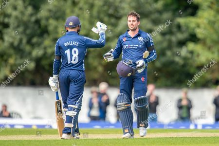 Scotland's Donald MacLeod celebrates with Craig Wallace (#18) after scoring 100 runs during the One Day International match between Scotland and Afghanistan at The Grange Cricket Club, Edinburgh