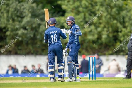 Stock Image of Scotland's Donald MacLeod (#10) is congratulated by Craig Wallace (#18) after scoring 100 runs during the One Day International match between Scotland and Afghanistan at The Grange Cricket Club, Edinburgh