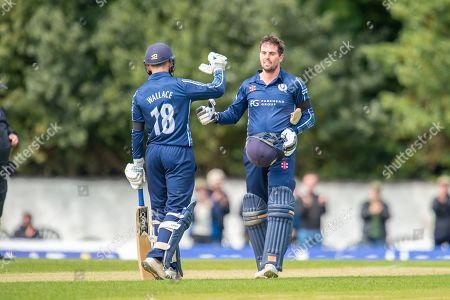 Stock Picture of Scotland's Donald MacLeod celebrates with Craig Wallace (#18) after scoring 100 runs during the One Day International match between Scotland and Afghanistan at The Grange Cricket Club, Edinburgh