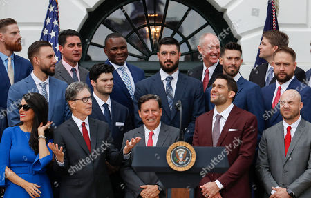 Red Sox Principal Owner John Henry, second from the left, gestures while he waits with from l-r, first row Henry's wife Linda Pizzuti, Tom Werner, Chairman of the Red Sox, players Nathan Eovaldi, and Steve Pearceas and others as they wait for President Donald Trump to arrive for a ceremony on the South Lawn of the White House in Washington, where Trump will honored the 2018 World Series Baseball Champion Boston Red Sox