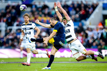 Camille Lopez of ASM Clermont Auvergne kicks under pressure from Gregory Alldritt of La Rochelle