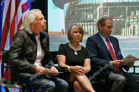 Virgin Galactic founder Sir Richard Branson, left, New Mexico Gov. Michelle Lujan Grisham and U.S. Sen. Tom Udall wait to speak during an event at the state capital, in Santa Fe, N.M. Branson announced Friday that his company will begin shifting operations from California to a spaceport and specialized runway in the New Mexico desert in final preparations for commercial flights
