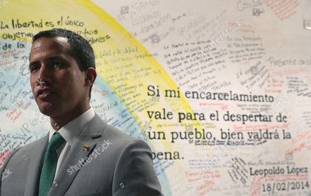 """Venezuela's opposition leader Juan Guaidó, who declared himself the interim-president of Venezuela, stands next to a mural that displays a quote by Leopoldo Lopez, founder of the Popular Will party, that reads in Spanish: """"If my imprisonment is worth the awakening of the people, then it was worth it,"""" at party headquarters in Caracas, Venezuela, . The 35-year-old national assembly president, who the U.S. and 50 other countries recognize as Venezuela's rightful leader, sat for an interview with The Associated Press at his party's headquarters on Friday"""