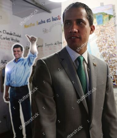 Venezuela's opposition leader Juan Guaidó, who declared himself the interim-president of Venezuela, stands near a life size cutout of the founder of the Popular Will party Leopoldo Lopez, at party headquarters in Caracas, Venezuela, . The 35-year-old national assembly president, who the U.S. and 50 other countries recognize as Venezuela's rightful leader, sat for an interview with The Associated Press on Friday