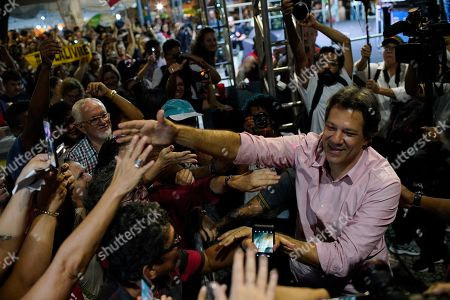 Fernando Haddad, who ran in the last presidential race backed by the Workers' Party, right, greets supporters during a protest against cuts in Brazil's public education sector at Cinelandia square, Rio de Janeiro, Brazil, . Students and teachers gathered in the city's center Friday, taking a stand against the administration of fair-right President Jair Bolsonaro