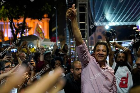 Stock Photo of Fernando Haddad, who ran in the last presidential race backed by the Workers' Party, right, greets supporters during a protest against cuts in Brazil's public education sector at Cinelandia square, Rio de Janeiro, Brazil, . Students and teachers gathered in the city's center Friday, taking a stand against the administration of fair-right President Jair Bolsonaro