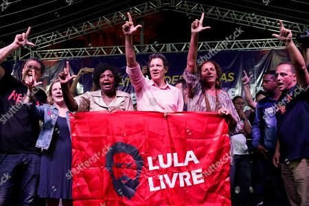 """Stock Picture of Fernando Haddad, center, who ran in the last presidential race backed by the Workers' Party, holds a banner that reads in Portuguese """"Free Lula"""" during a protest against cuts in Brazil's public education sector at Cinelandia square, Rio de Janeiro, Brazil, . Students and teachers gathered in the city's center Friday, taking a stand against the administration of fair-right President Jair Bolsonaro"""