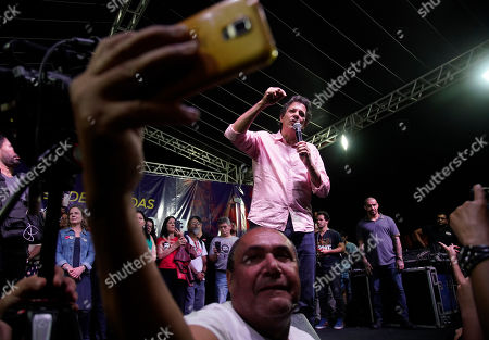 A man takes a selfie while Workers' Party former presidential candidate Fernando Haddad in the background, during a protest against cuts in Brazil's public education sector at Cinelandia square, Rio de Janeiro, Brazil