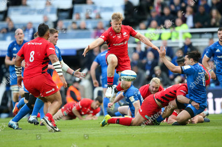 James Lowe of Leinster passes and Jackson Wray of Saracens leaps