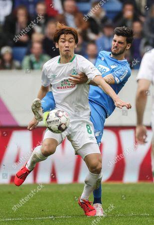 Hoffenheim's Florian Grillitsch (behind) in action against Bremen's Yuya Osako during the German Bundesliga soccer match between TSG 1899 Hoffenheim and SV Werder Bremen in Sinsheim, Germany, 11 May 2019.