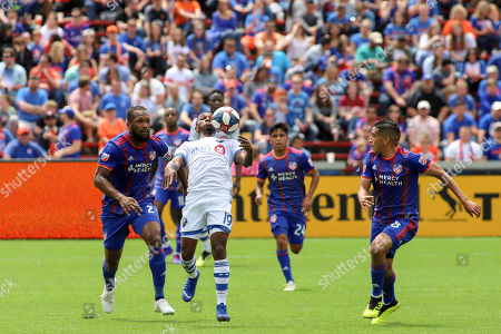 Omar Browne (center) of the Montreal Impact attempts to play the ball past Kendall Waston (left) and Victor Ulloa (right) of FC Cincinnati during an MLS soccer game between FC Cincinnati and Montreal Impact at Nippert Stadium in Cincinnati, Ohio